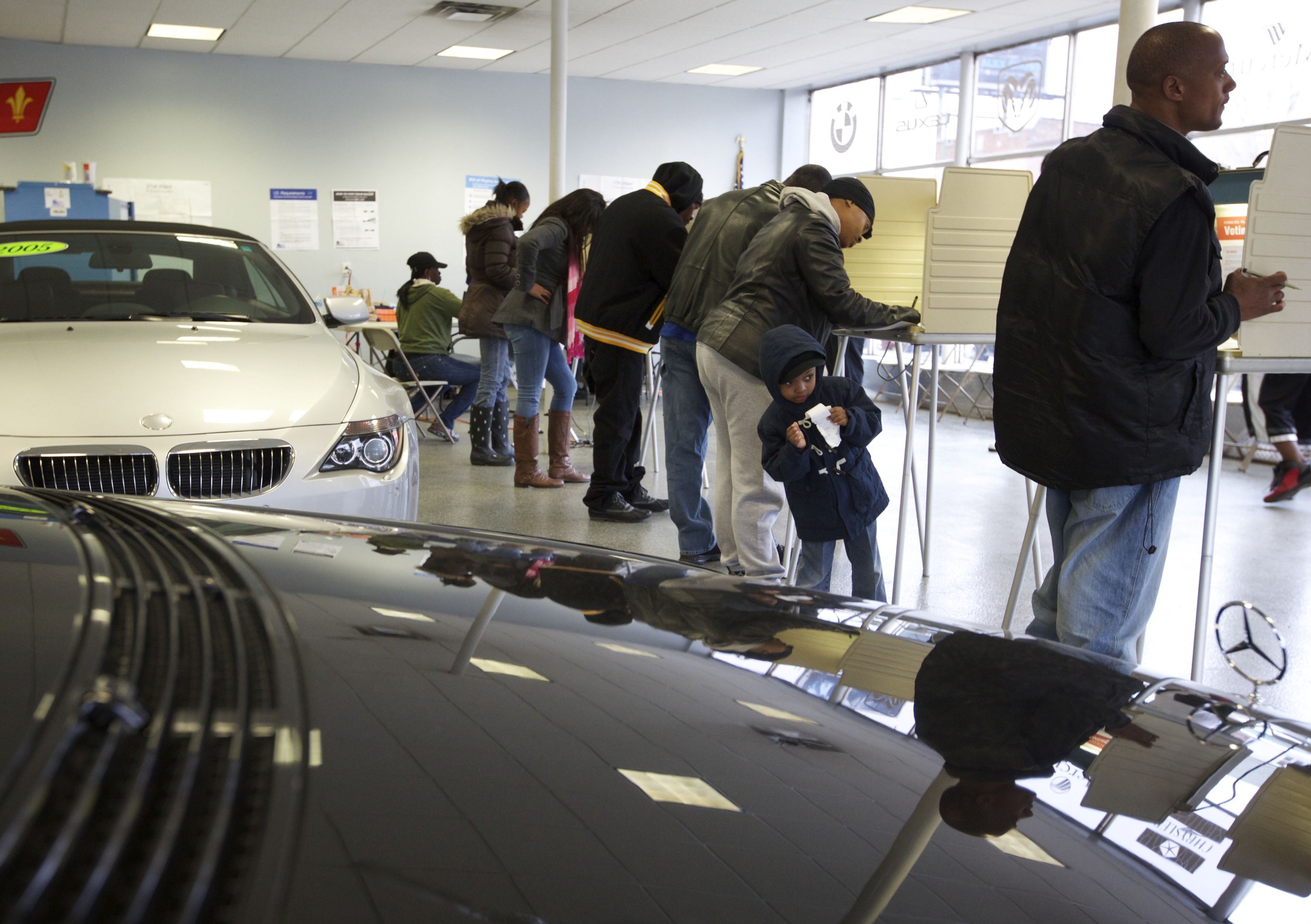 Voters cast their ballots next to cars during the U.S. presidential election at Sam's Auto Sales in Chicago