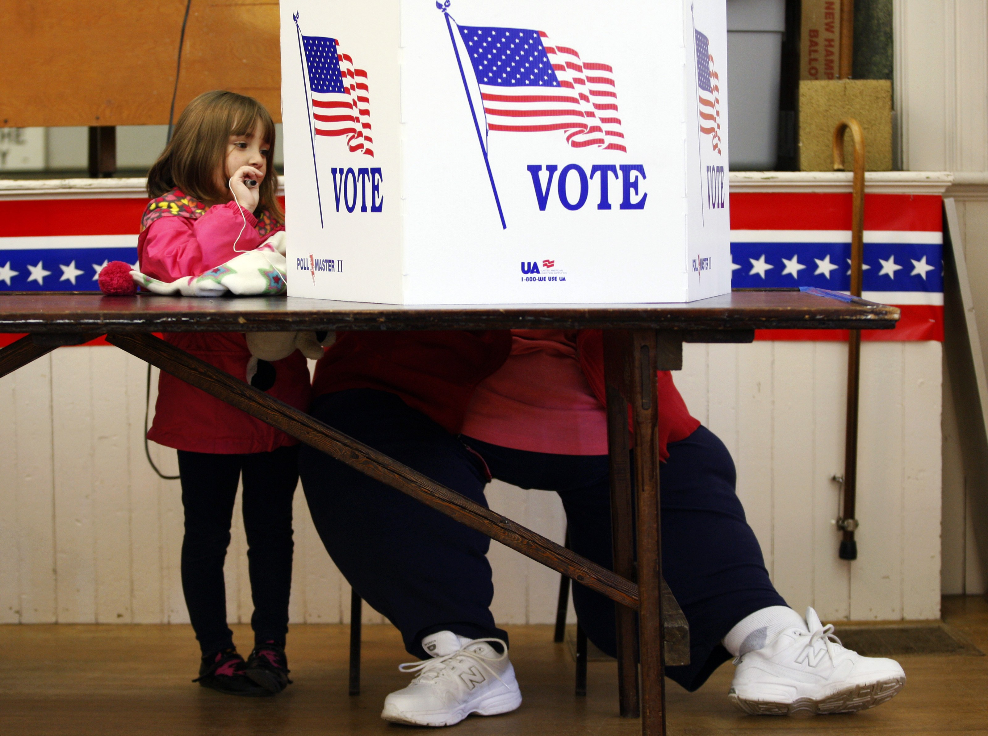 A girl watches as her grandmother votes at the old Town Hall during the U.S. presidential election in Bristol