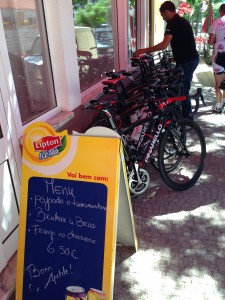 Bicicletas e equipamentos de ciclismo contrastam com a tranquilidade de um restaurante local